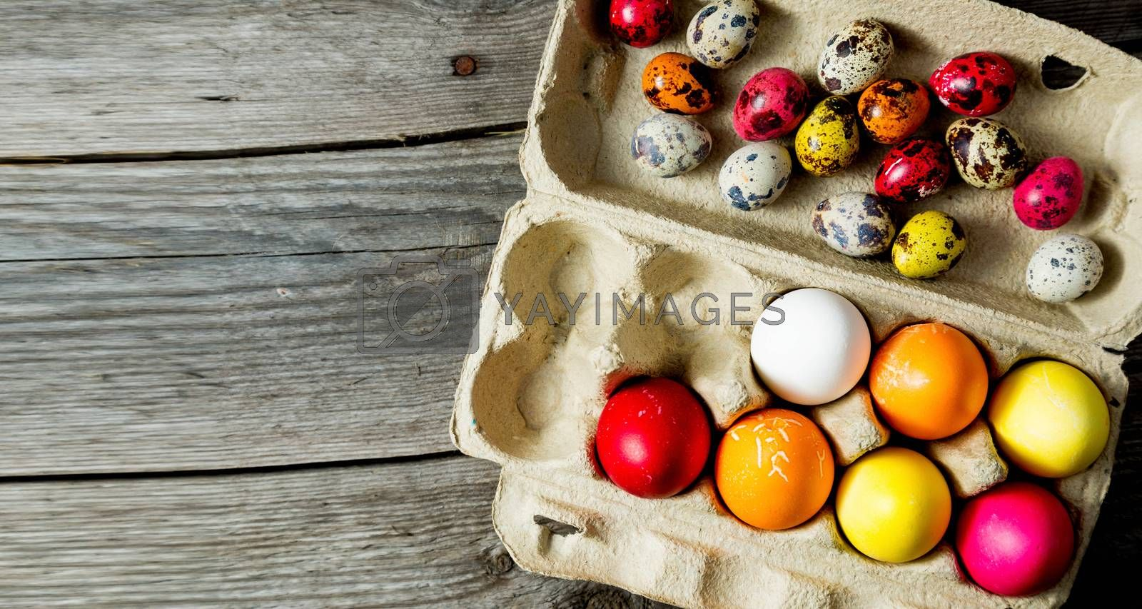 Dyed easter eggs in cardboard box on wooden background. Easter background.