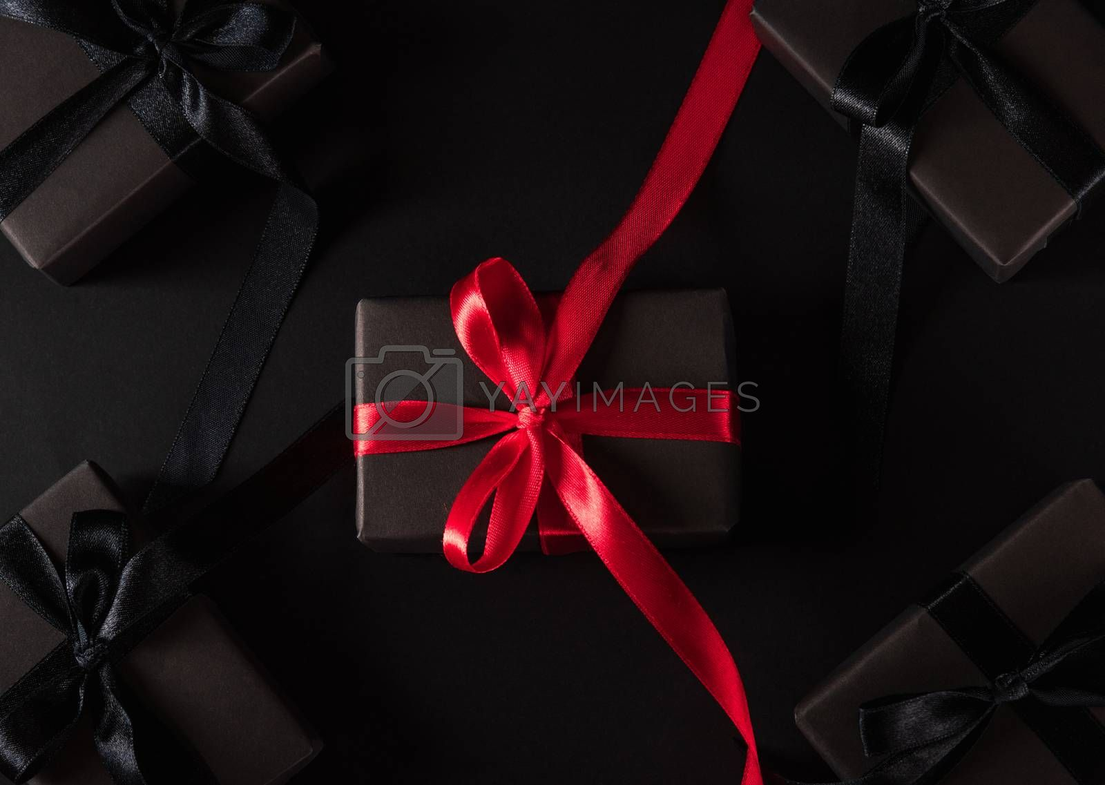 Black Friday sale shopping concept, Top view of gift box wrapped black paper and black bow ribbon present around the box with a red ribbon, studio shot on dark background