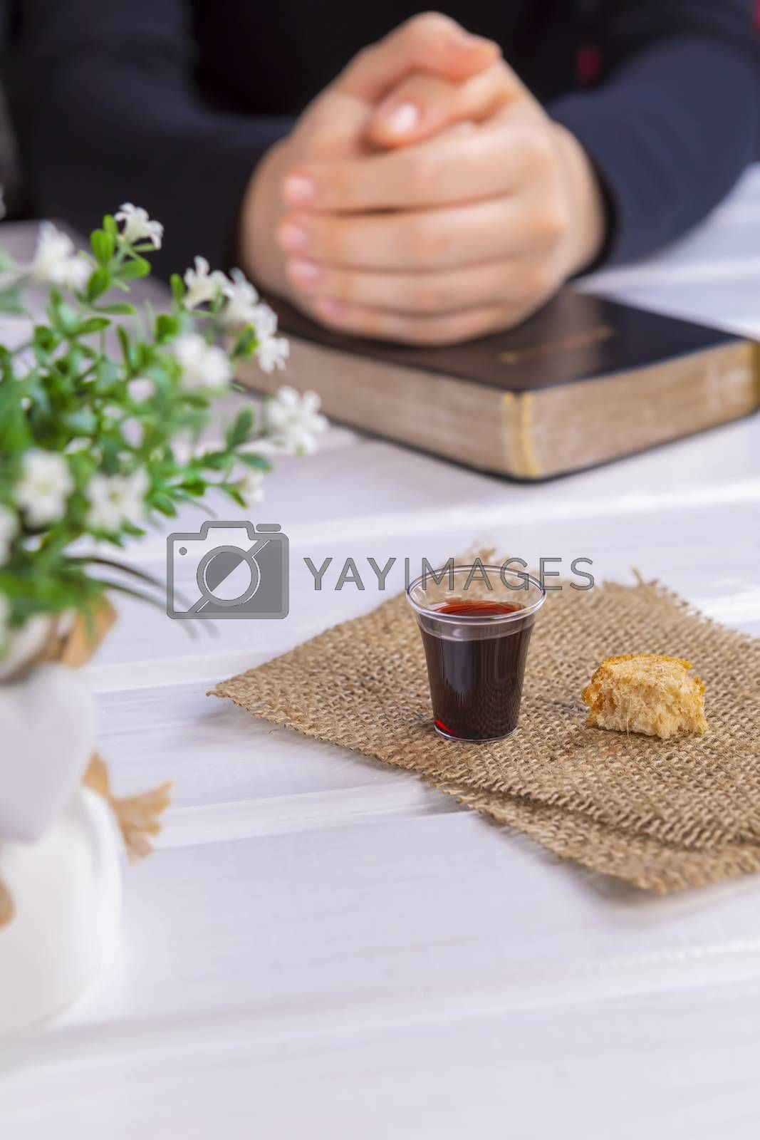Young woman praying and Taking communion  - the wine and the bread symbols of Jesus Christ blood and body with Holy Bible. Easter Passover and Lord Supper concept Focus in glass.