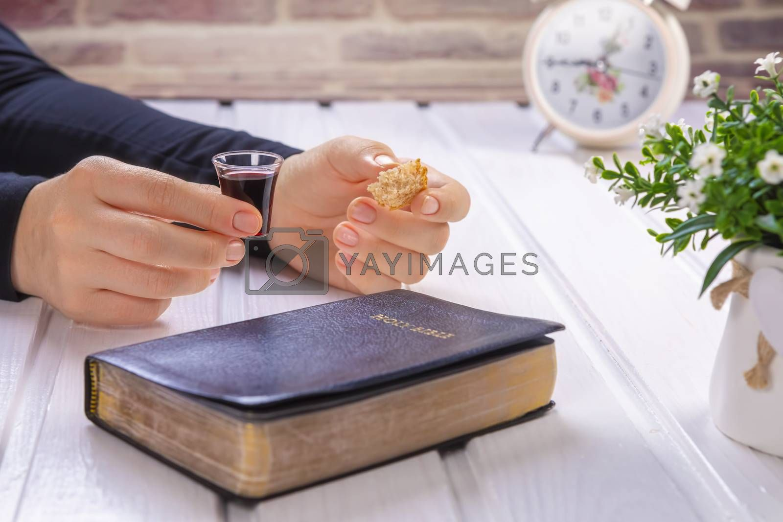 Young woman praying and Taking communion  - the wine and the bread symbols of Jesus Christ blood and body with Holy Bible. Easter Passover and Lord Supper concept Focus on glass.