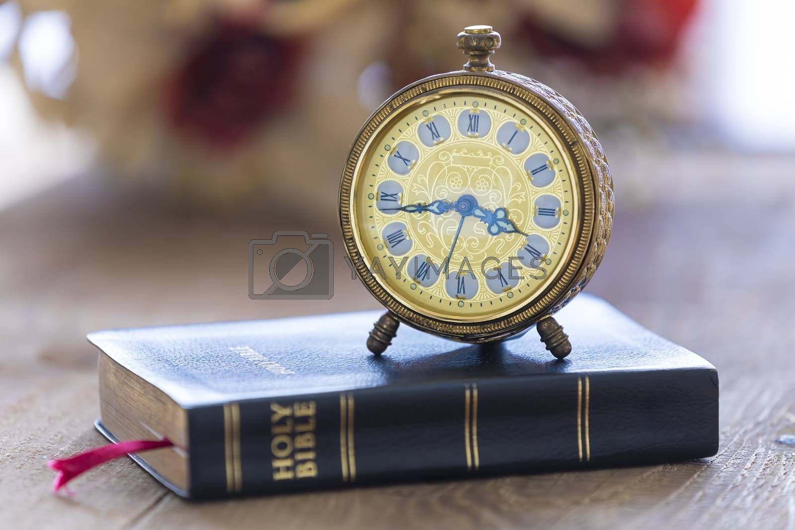 Old alarm clock on Holy bible with flowers on wooden table background