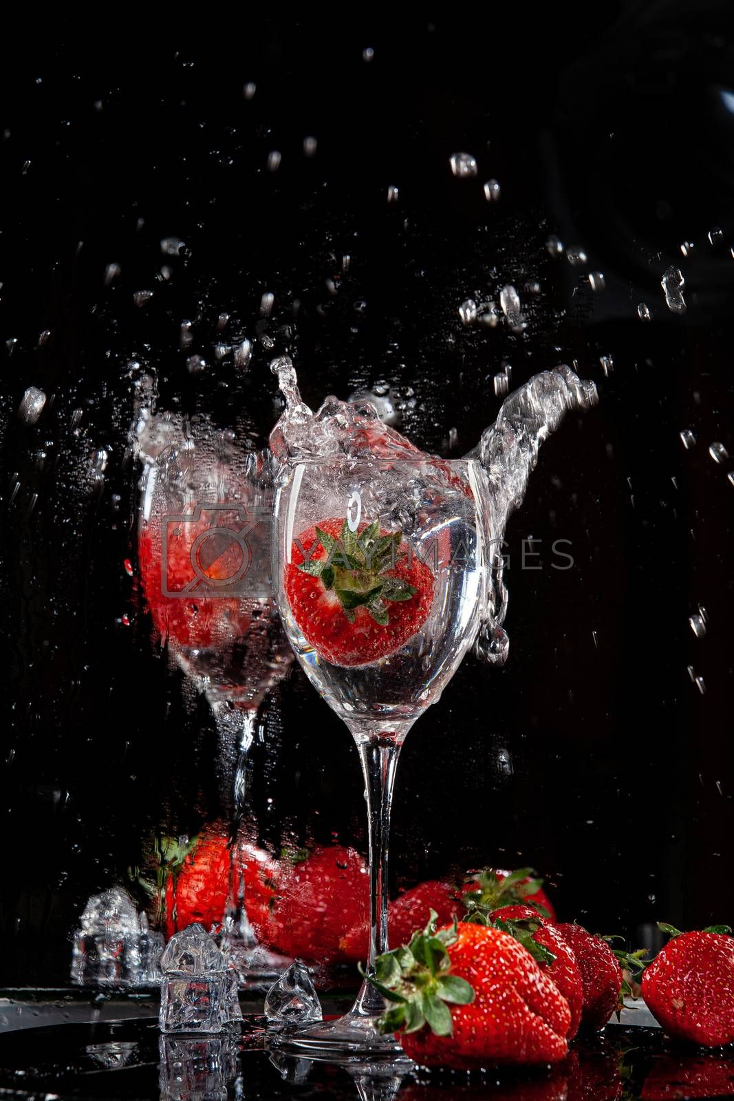 Strawberry falling into the glass with water