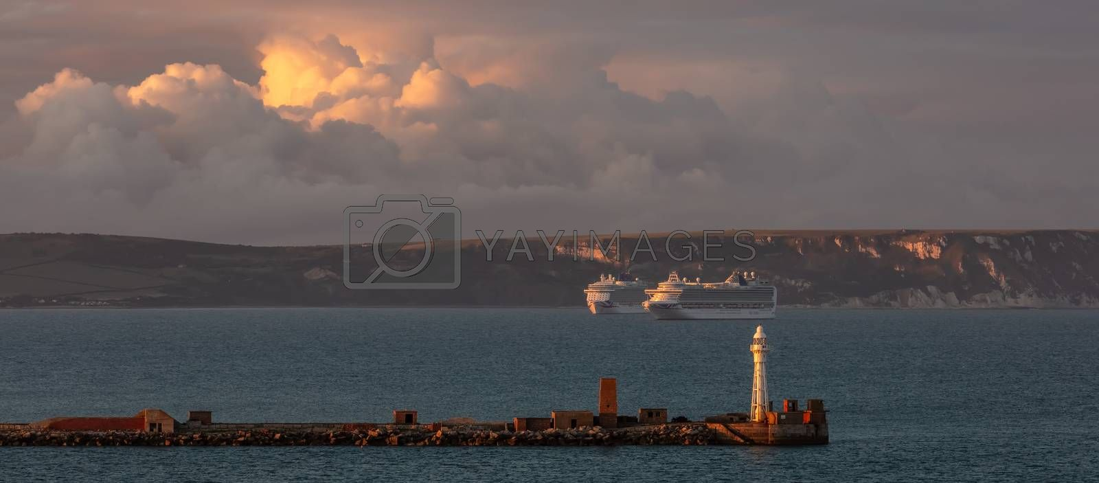 Portland, United Kingdom - July 1, 2020: Beautiful panoramic shot of Portland harbour lighthouse with two P&O cruiseships anchored in the distance in Weymouth Bay. Beautiful sunset clouds.
