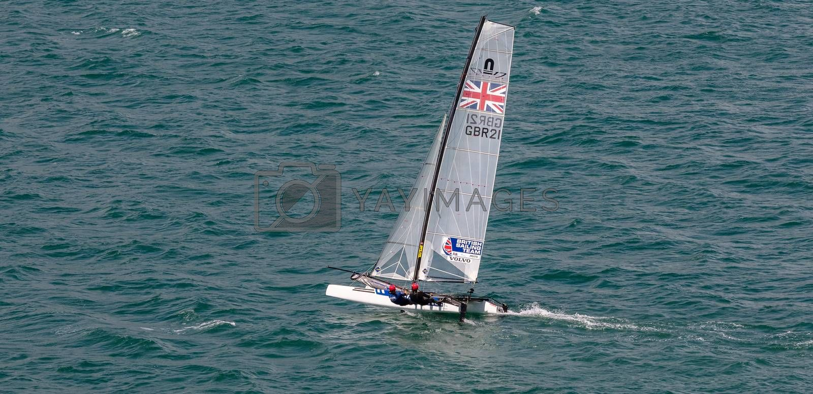 Portland harbour, United Kingdom - July 2, 2020: High Angle aerial panoramic shot of racing catamaran of the British Sailing Team. Two sailors on it wearing red helmets, British flag on the sails.