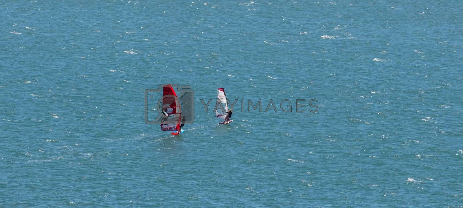Portland harbour, United Kingdom - July 2, 2020: High Angle aerial panoramic shot of two sail boards with professional surfers on them racing in Portland harbour.