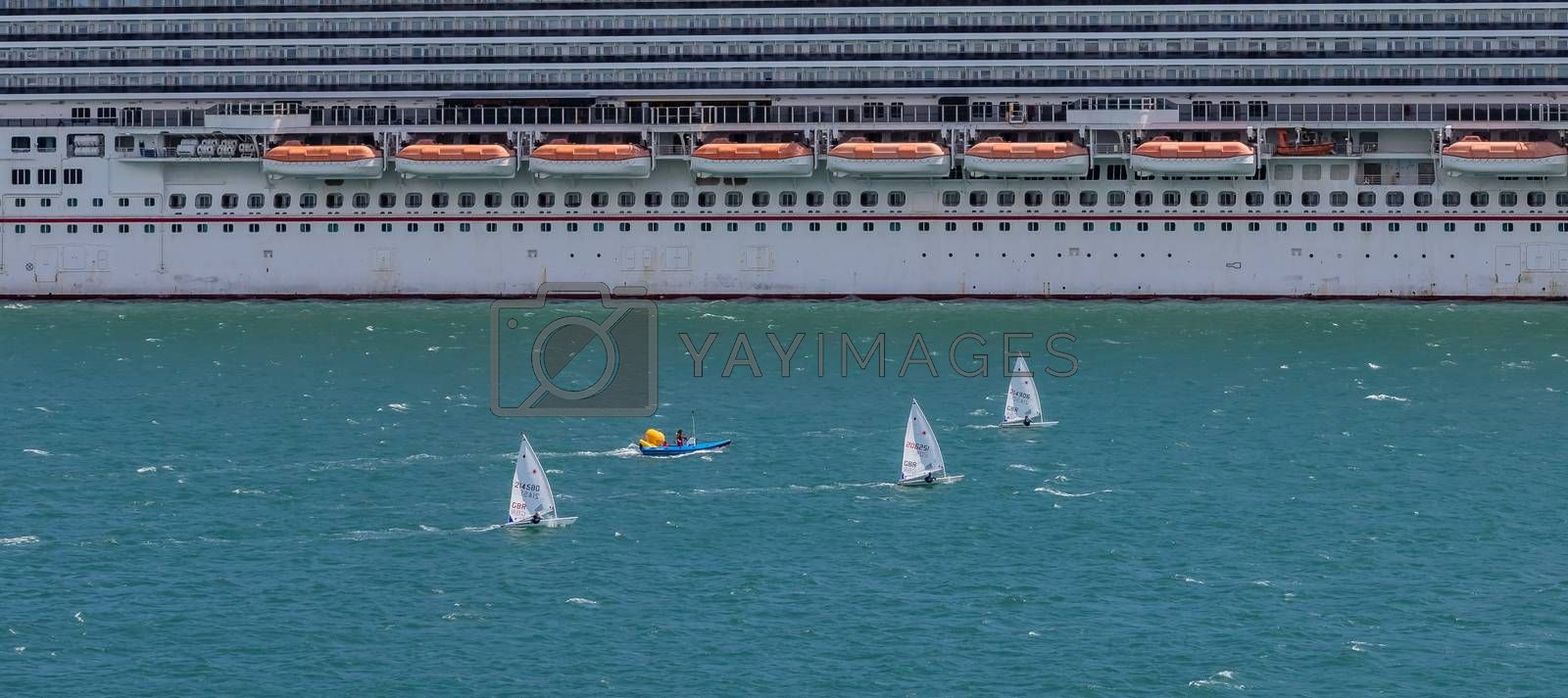 Portland harbour, United Kingdom - July 2, 2020: High Angle aerial panoramic shot of the laser class sailing racing dinghies and a rescue boat sailing by a huge cruise ship in Portland harbour.