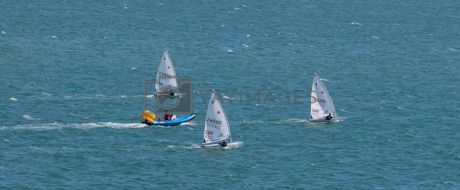 Portland harbour, United Kingdom - July 2, 2020: High Angle aerial panoramic shot of the laser class sailing racing dinghies and a rescue boat in Portland harbour.