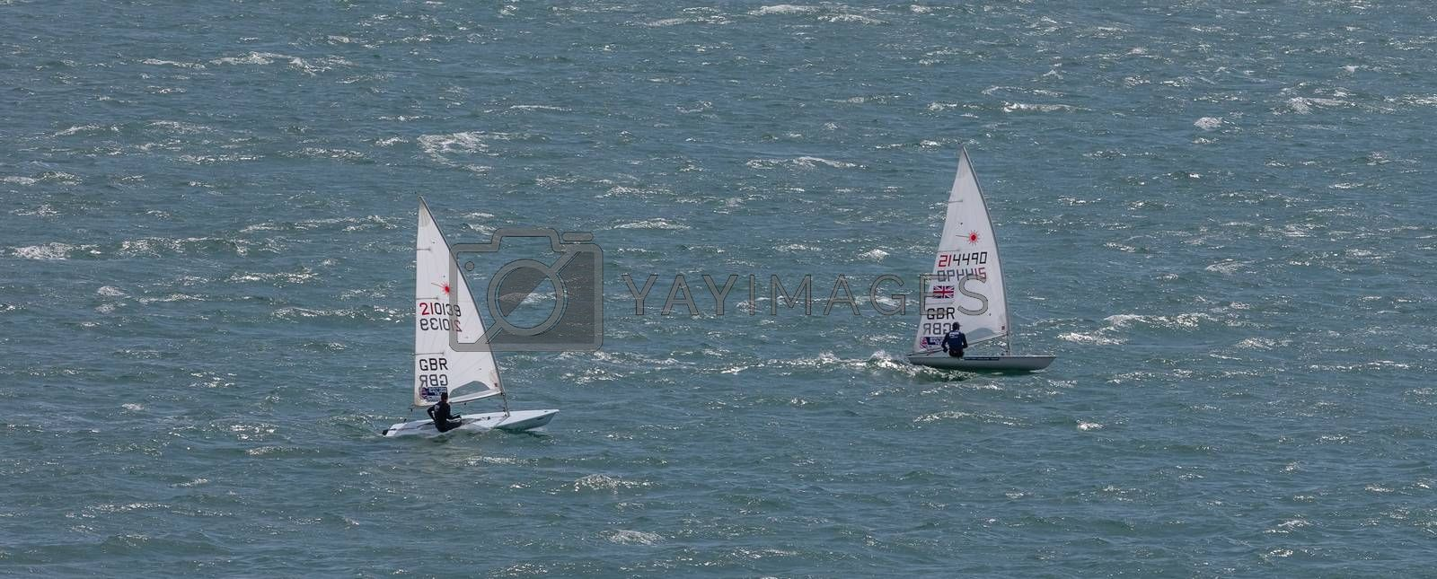 Portland harbour, United Kingdom - July 3, 2020: High Angle aerial panoramic shot of two laser class racing dinghies in Portland harbour.