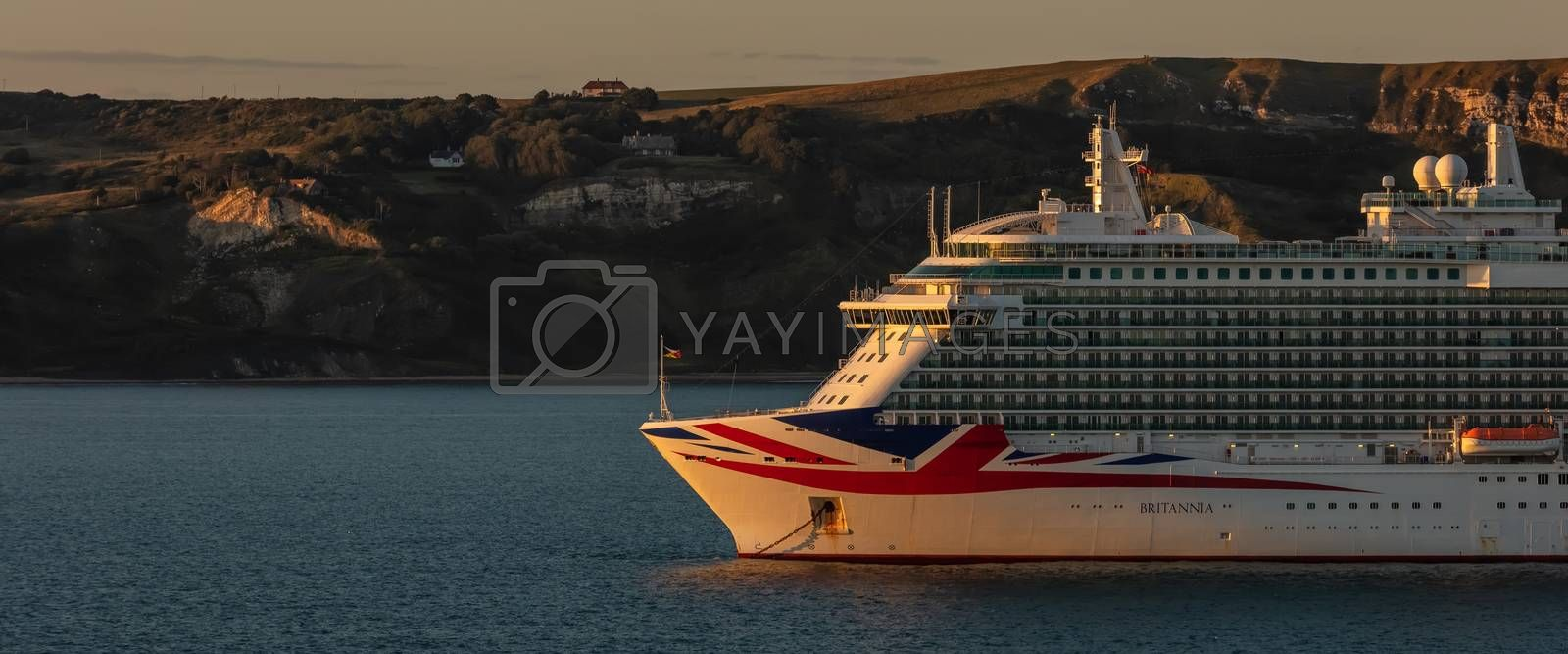 Weymouth Bay, United Kingdom - July 6, 2020: Beautiful panoramic shot of P&O cruise ship Britannia anchored in Weymouth Bay at sunset.