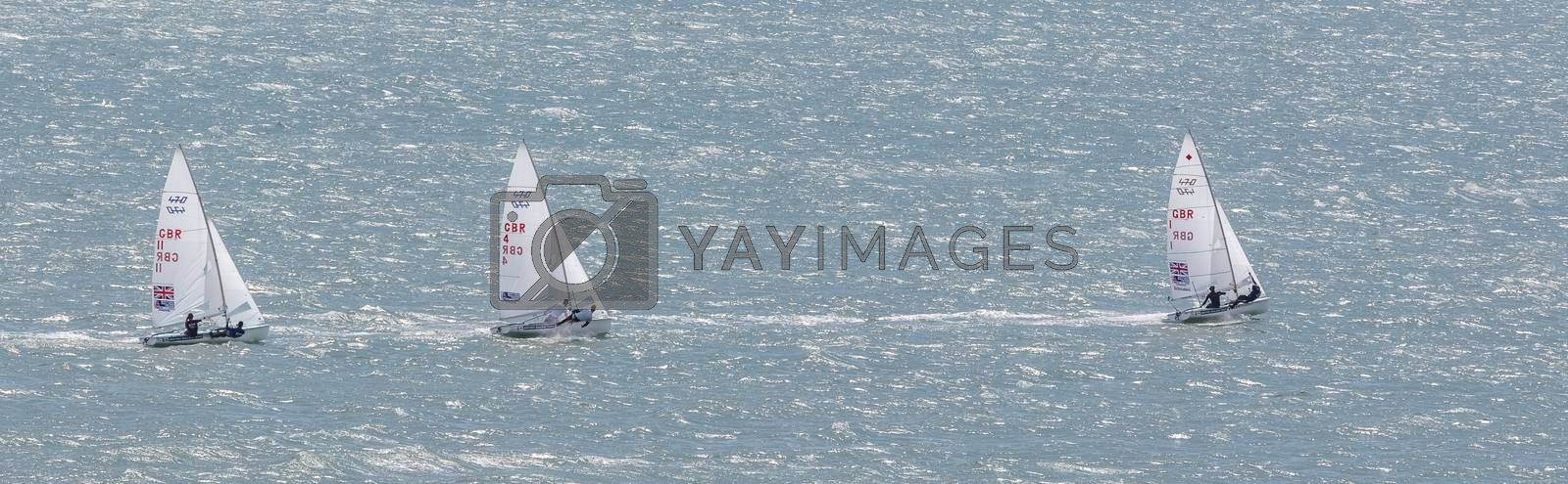 Portland harbour, United Kingdom - July 3, 2020: High Angle aerial panoramic shot of three laser class racing dinghies with one of them sailing way ahead of the first two