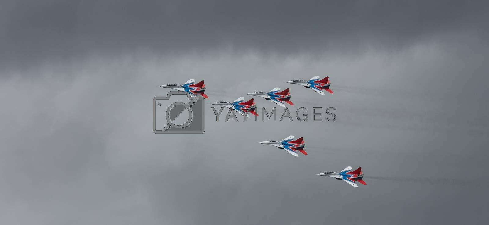 Barnaul, Russia - September 18, 2020: A low angle shot of Strizhi MiG-29 fighter jet squadron performing stunts during an aeroshow.