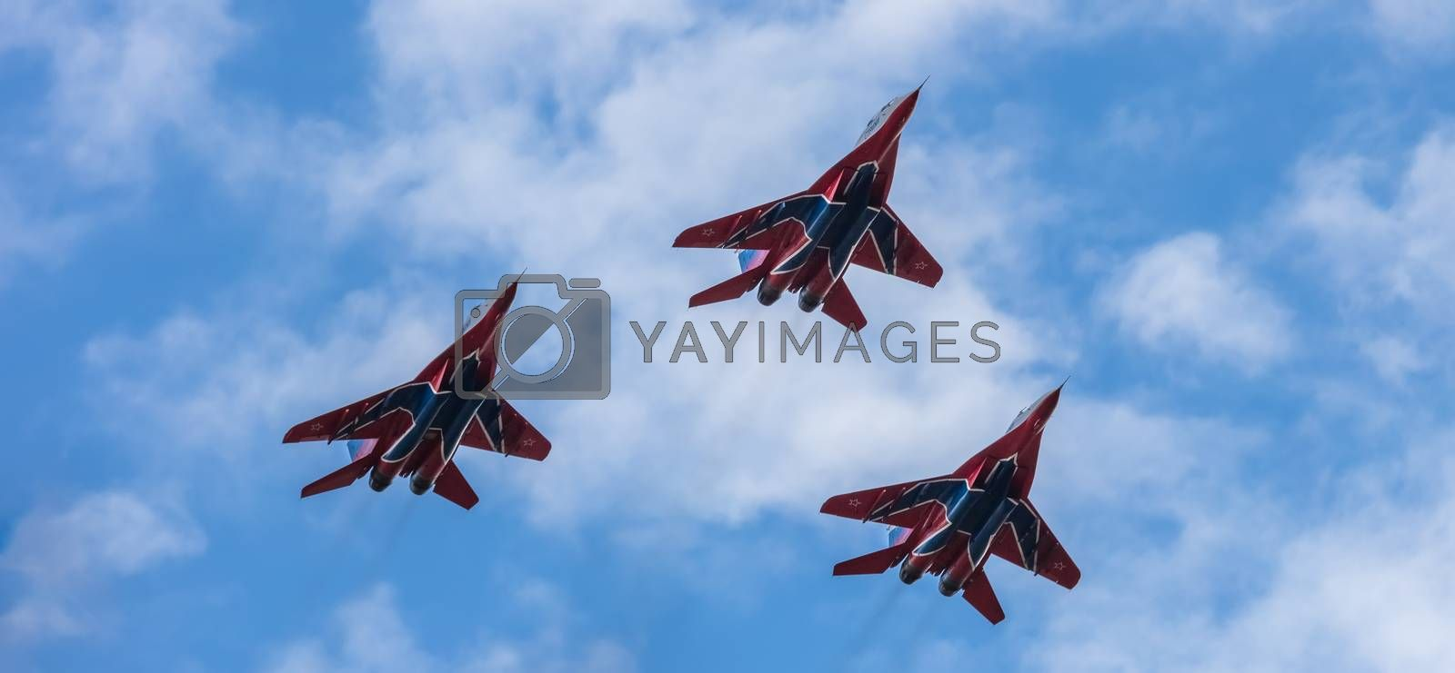 Barnaul, Russia - September 18, 2020: A low angle close-up shot of Strizhi MiG-29 jet squadron performing stunts during an aeroshow. Blue cloudy sky as a background.