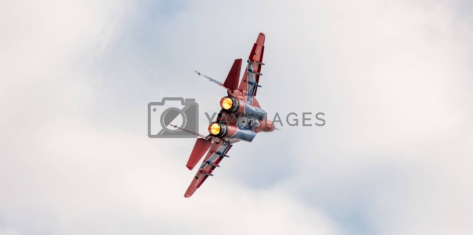 Barnaul, Russia - September 19, 2020: A close-up shot of Strizhi MiG-29 fighter jet performing stunts during an aeroshow. White cloudy sky as a background.