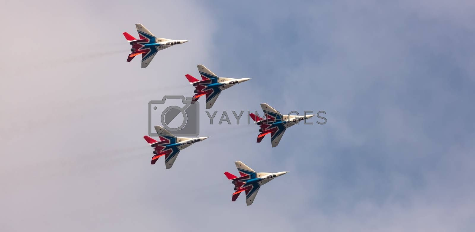 Barnaul, Russia - September 19, 2020: A low angle shot of Strizhi MiG-29 fighter jet squadron performing stunts during an aeroshow. Blue cloudy sky as a background.
