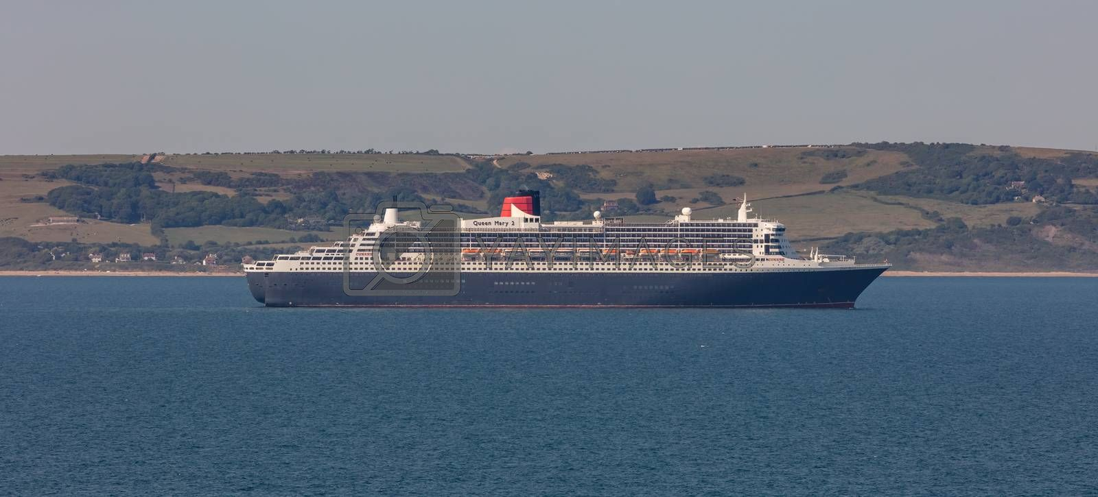 Weymouth Bay, United Kingdom - June 25, 2020: Beautiful panoramic shot of Cunard cruise ship Queen Mary 2 anchored in Weymouth Bay.