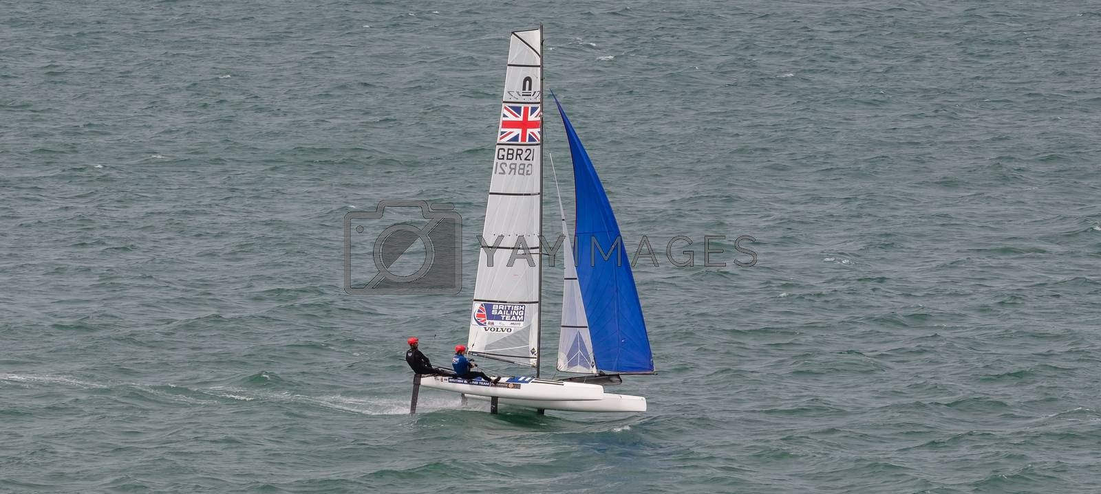 Portland harbour, United Kingdom - July 1, 2020: High Angle aerial panoramic shot of racing catamaran of the British Sailing Team. Two sailors on it wearing red helmets, British flag on the sails.