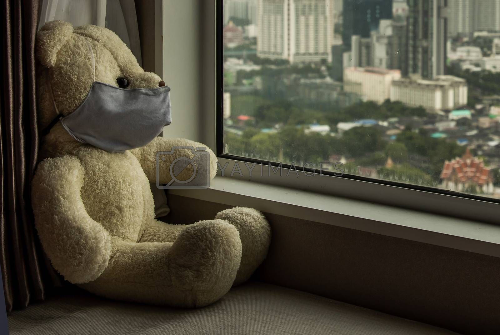 Sad teddy bear in protective medical masks sits on windowsill and looks out window. Stay at home quarantine coronavirus pandemic prevention, Virus outbreak in a world. No focus, specifically.
