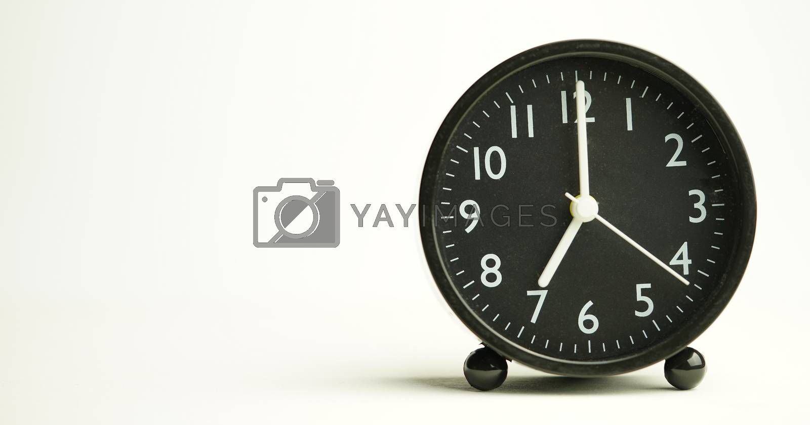 Decorative close-up black alarm clock for 7 hours isolated on white background with copy space.