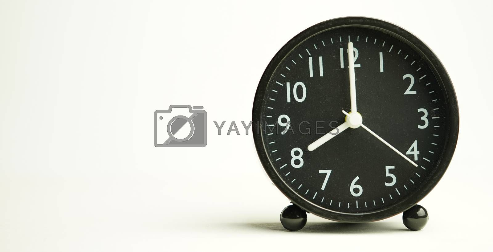 Decorative close-up black alarm clock for 7 hours isolated on white background with abstract copy space, start time of working day.