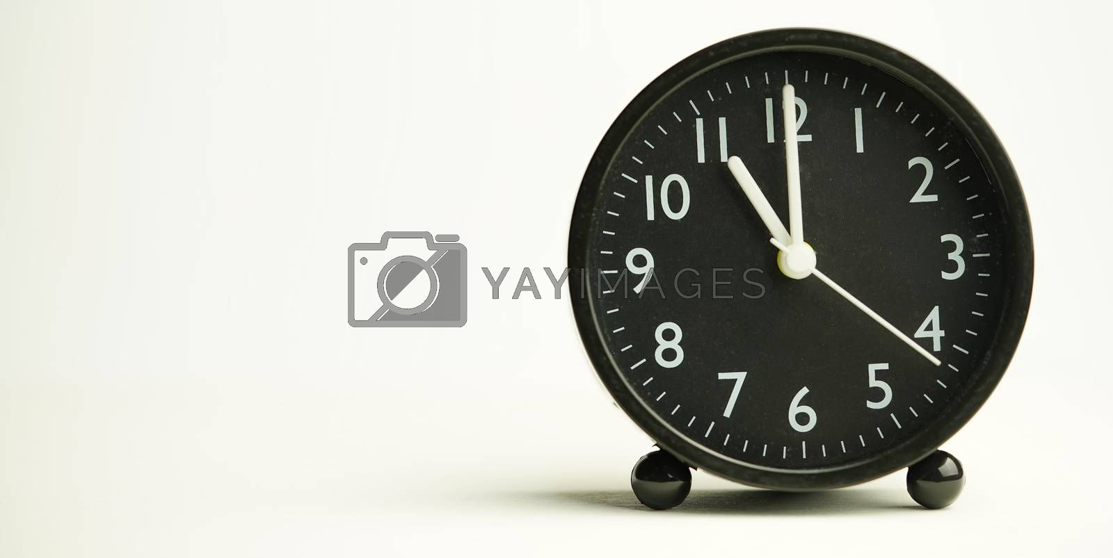 Decorative close-up black analog alarm clock for 10 o'clock isolated on white background with abstract copy space, start time of working day.