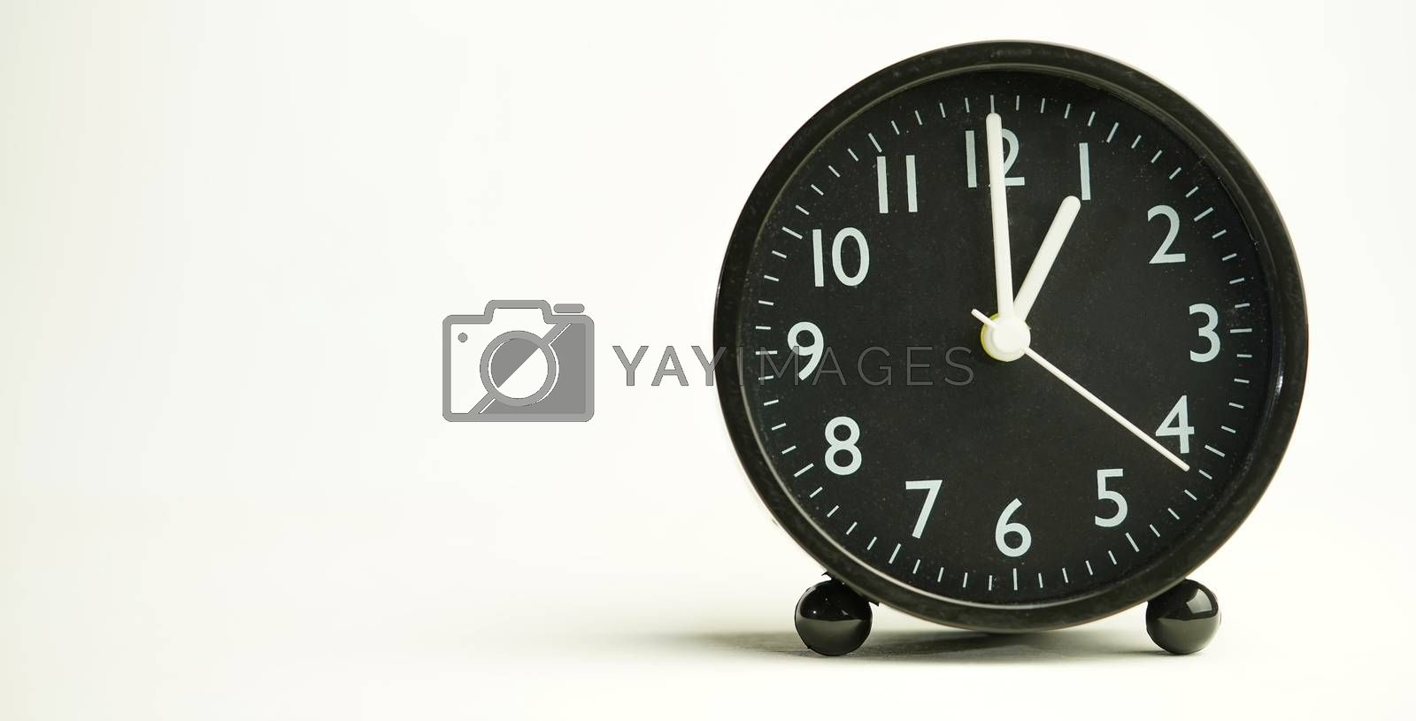 Decorative close-up black analog alarm clock for 13 o'clock separating white background with copy space.