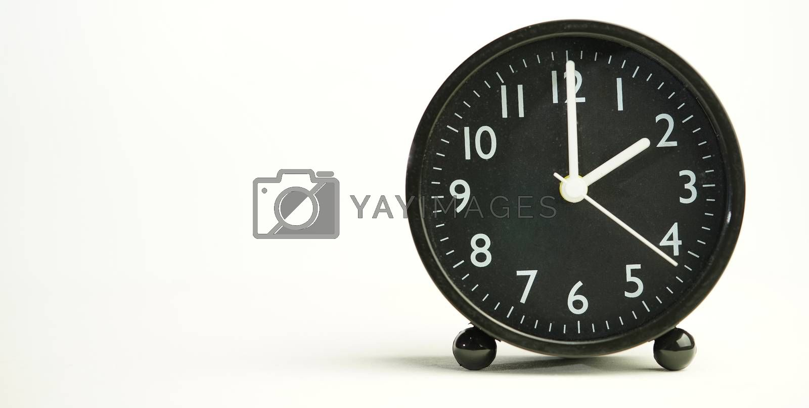 Decorative close-up black analog alarm clock for 2 o'clock, separate white background with copy space.