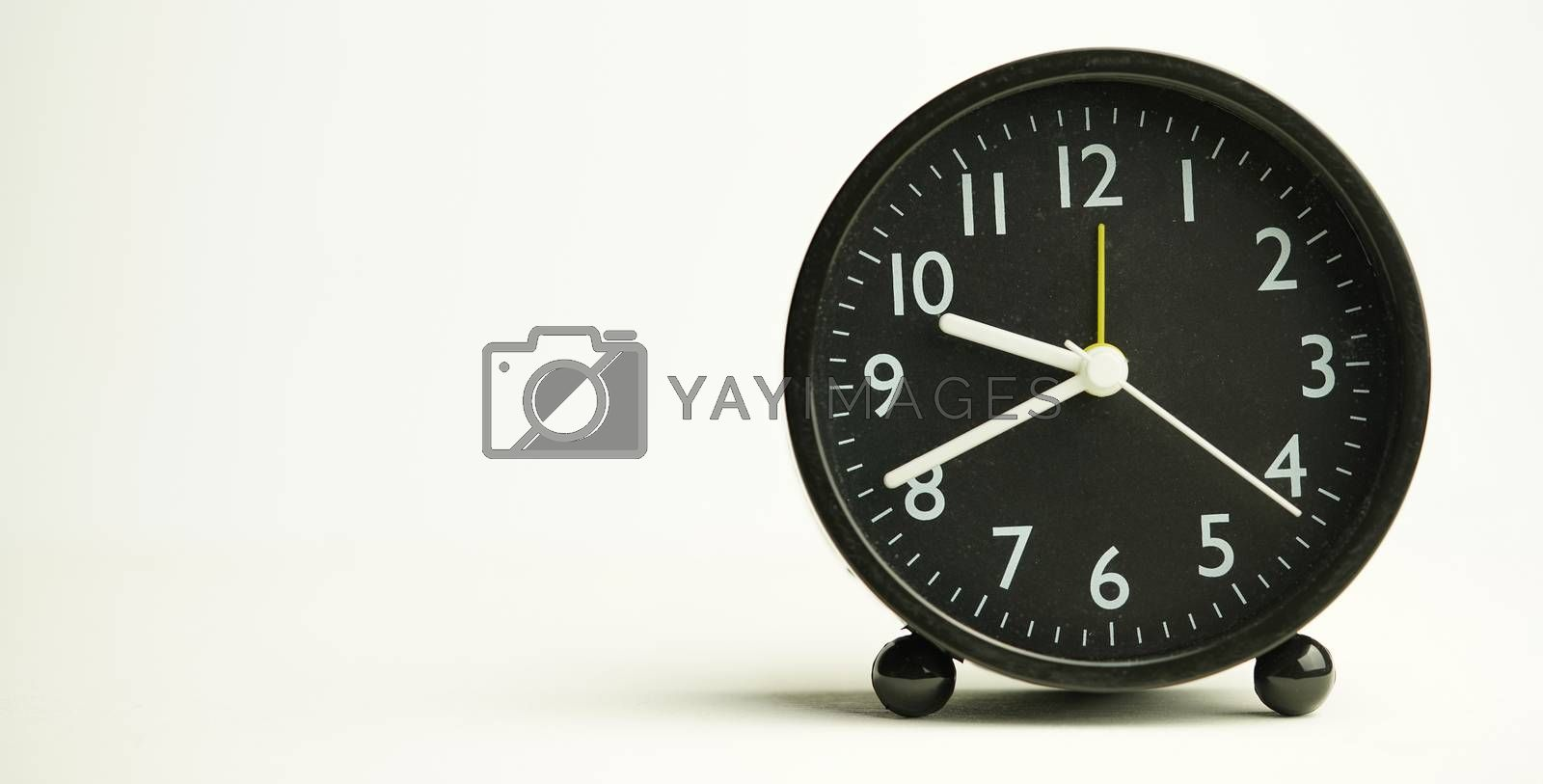 Decorative close-up black alarm clock at 9: 41min, isolated white background with abstract copy space, start time of working day.