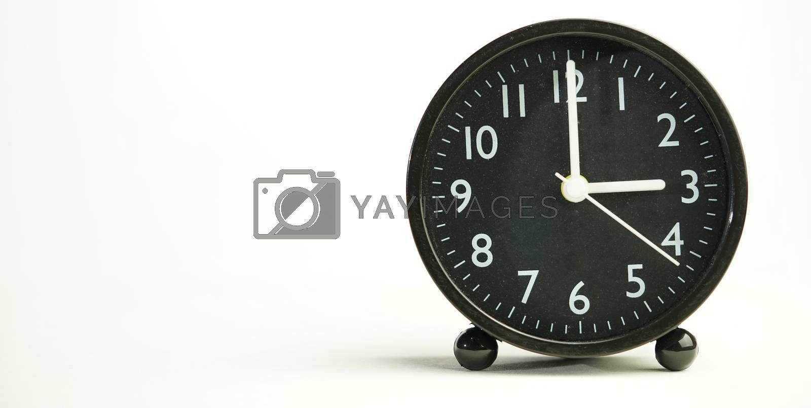 Decorative close-up black analog alarm clock for 3 o'clock or 15 o'clock, separate white background with copy space.
