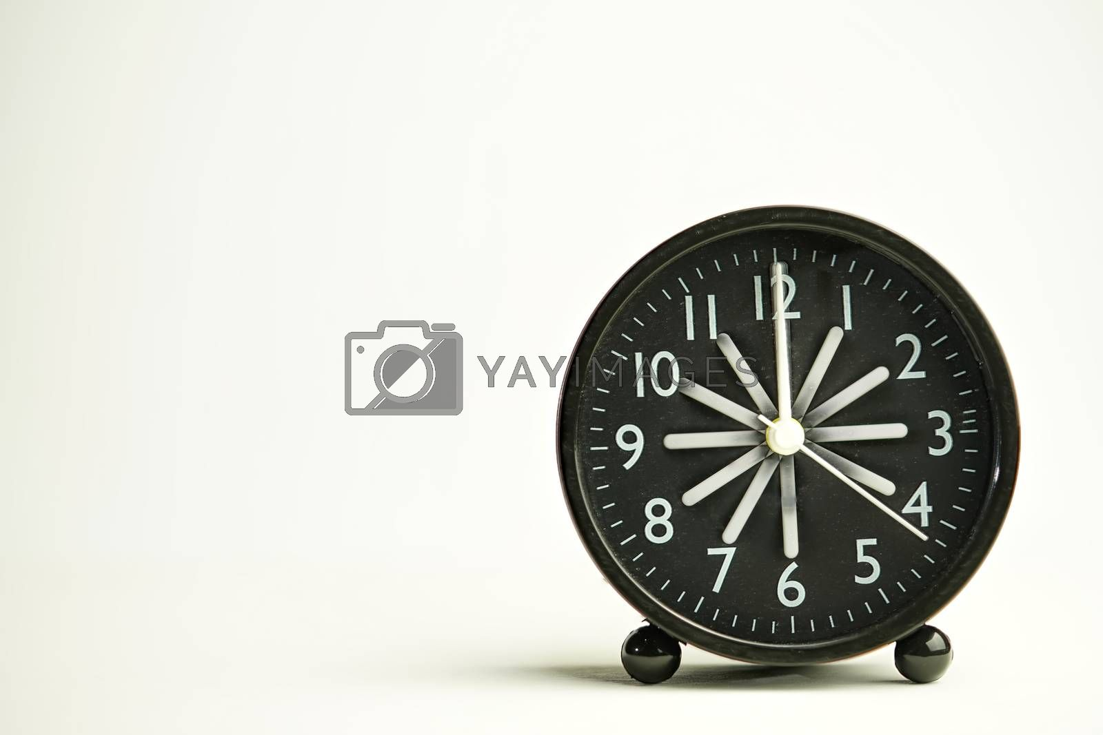 Abstract black analog alarm clock close-up inside being dusted island vintage style isolated white background with copy space. Use the Radius Blur technique.