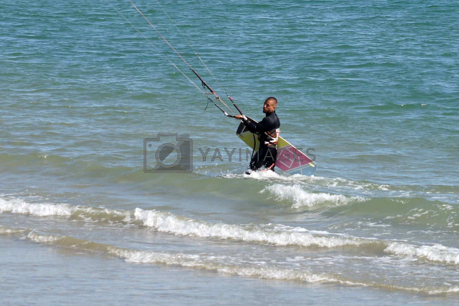 Varna, Bulgaria - September, 19, 2020: a man comes out of the sea with a kiteboard