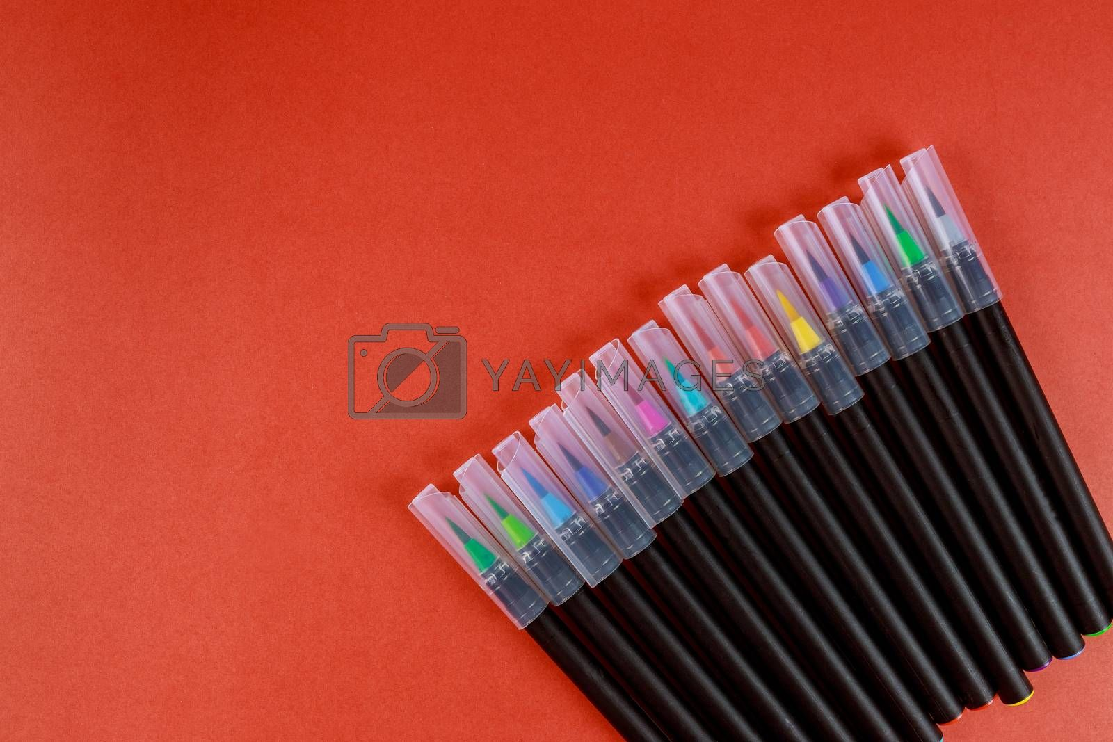 Sets of colored watercolor brush pens red background School Supplies