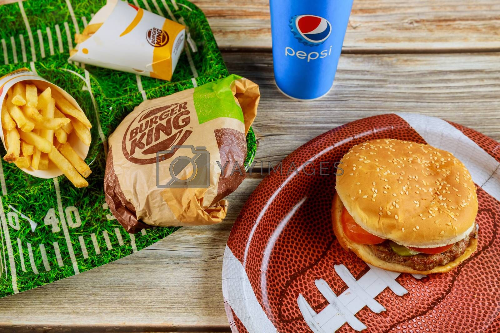 17 January 2020 Chicago IL: Burger king set french fries and cola drink for watching a football game. Super Bowl day party on wooden table