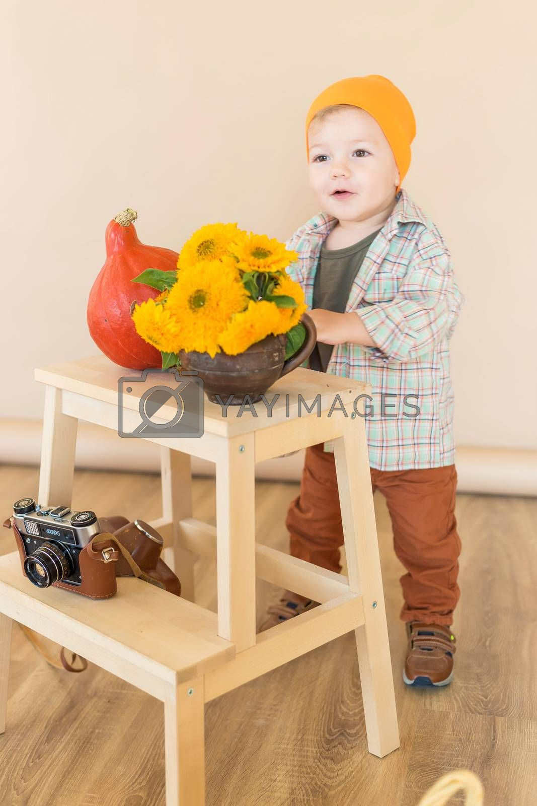 .The little boy stands in the autumn photo zone in the studio and smiles.