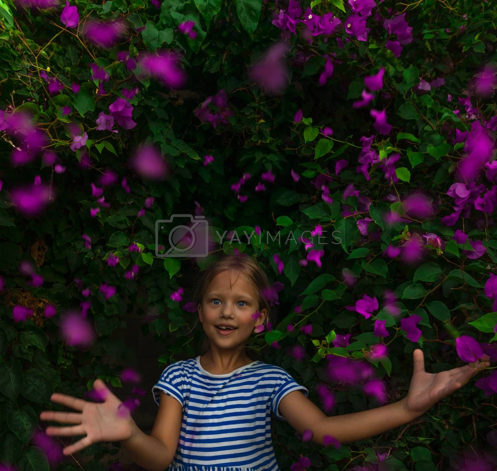 Portrait of a Cute Little Girl Among Beautiful Fresh Purple Flowers on the Bush. Sweet Child over Floral Background. Young Happy Baby Gardener.