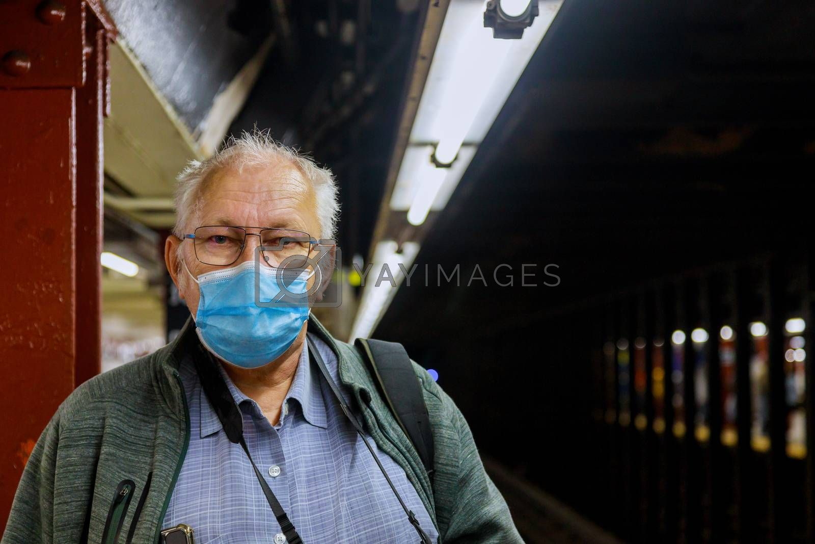 Old man in medical mask standing in the subway coronavirus epidemic in to expect train subway