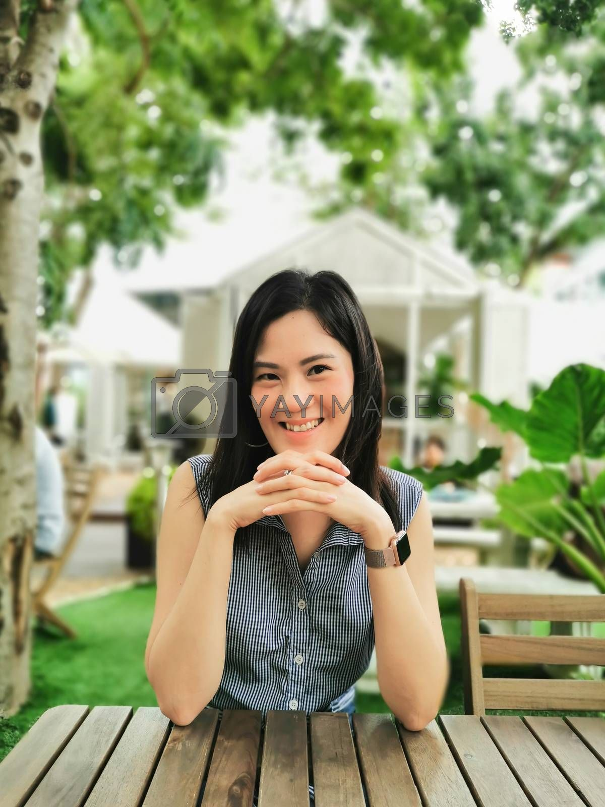 An Asian woman feeling happy and smiling in the garden