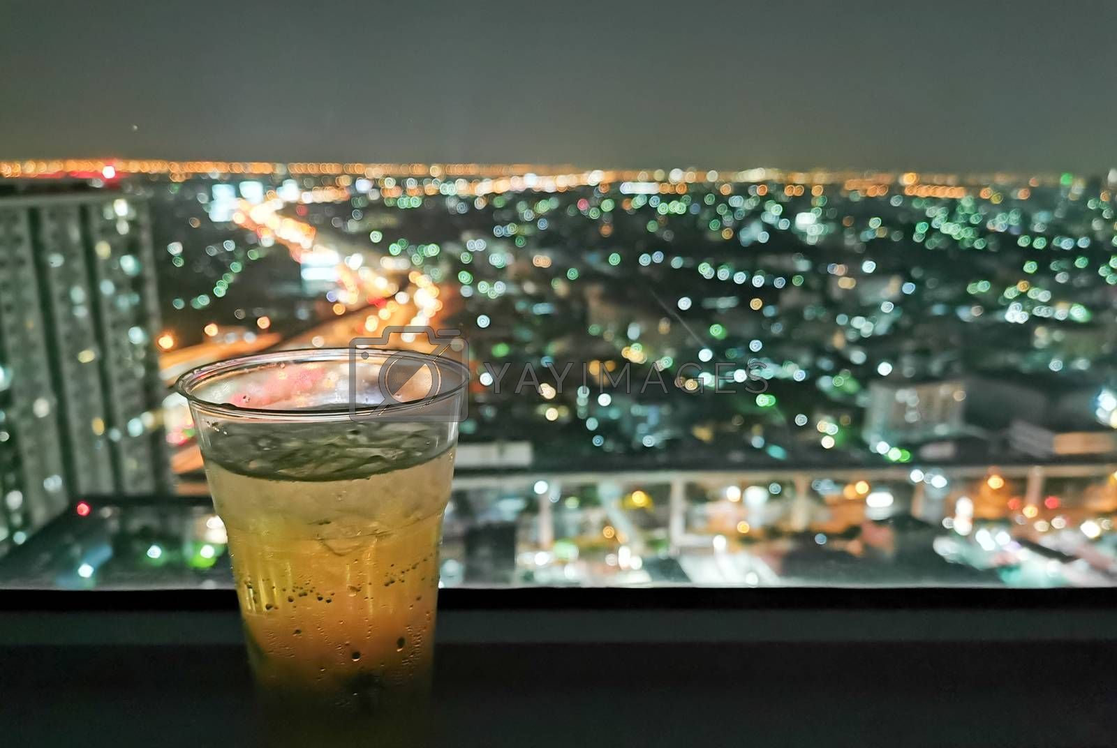 A glass of beer with cityscape from high condominium view at night.