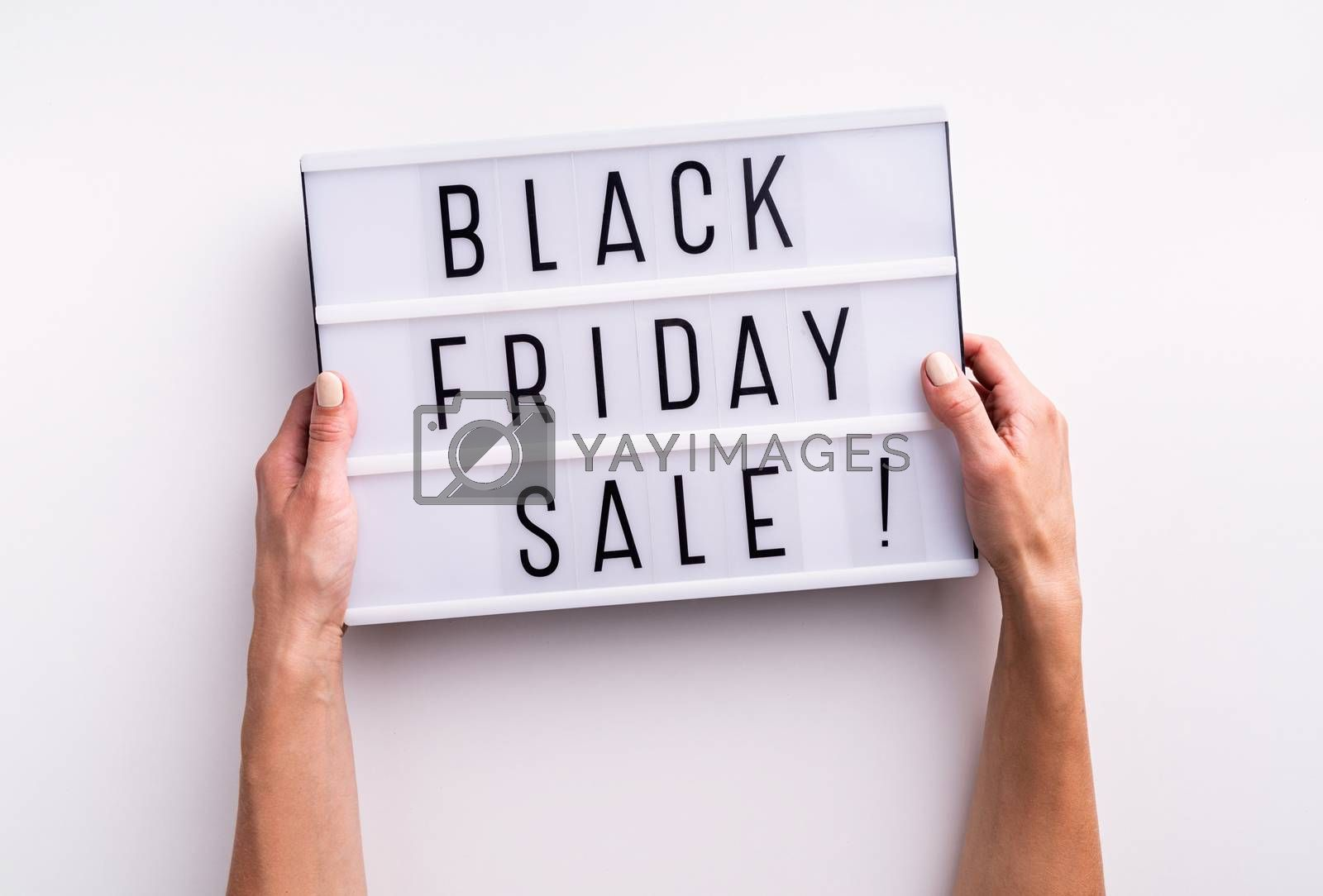 Woman hands holding lightbox with words Black Friday Sale on white background. Top view flat lay