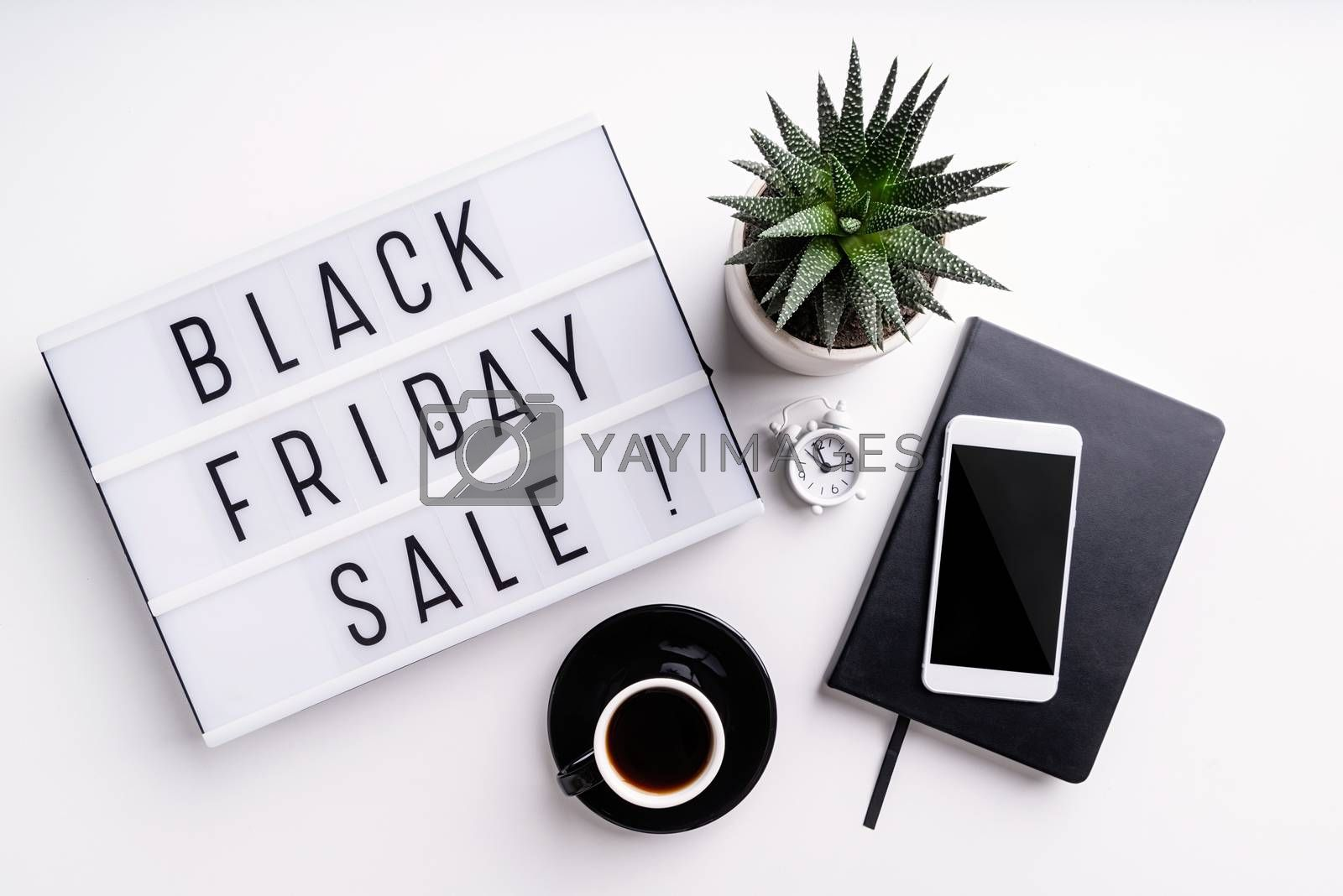 Black Friday shopping sale concept. Black Friday Sale words on lightbox with cup of coffee, mobile phone and potplant top view flat lay on white background