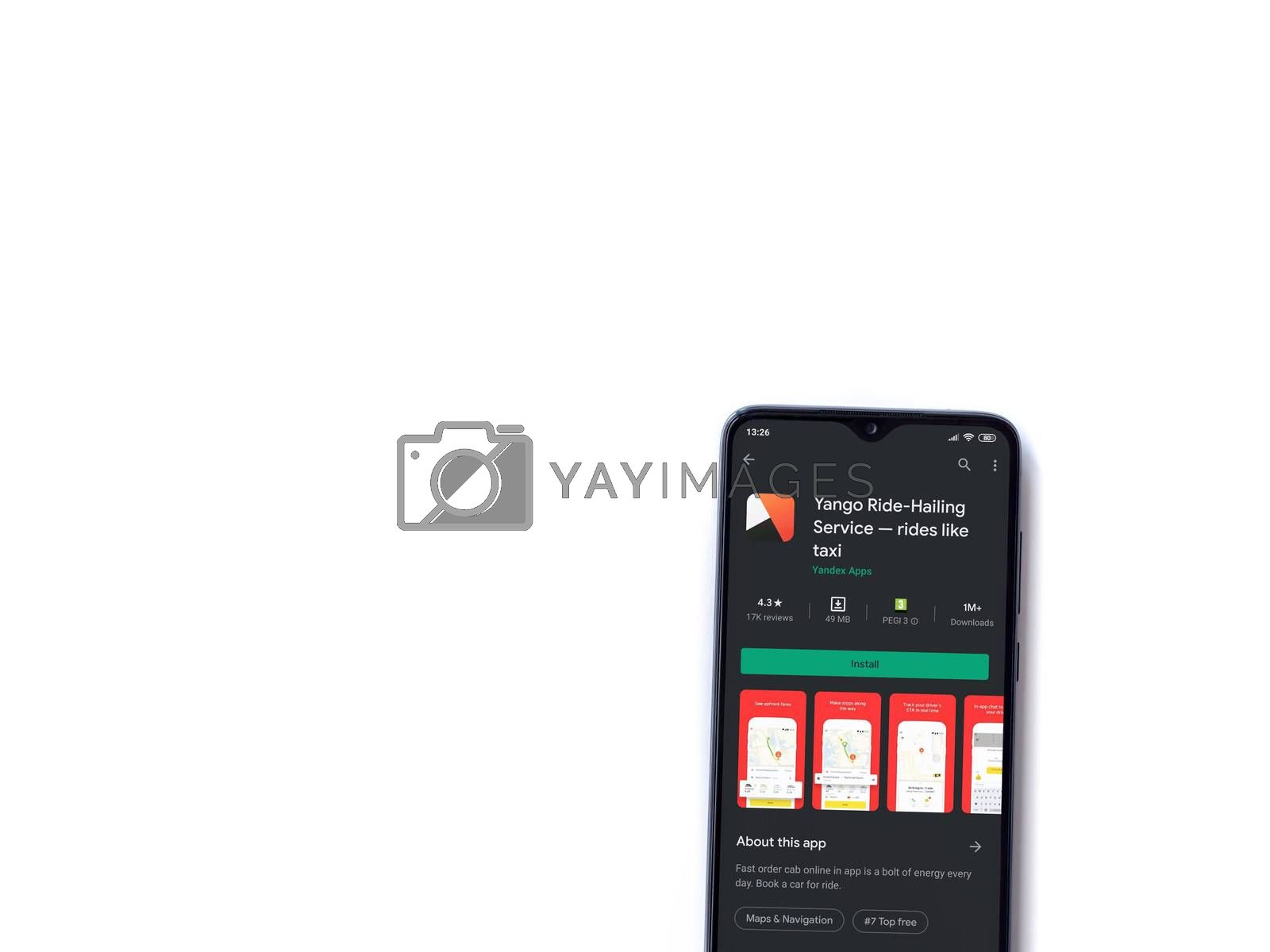 Lod, Israel - July 8, 2020: Yango Ride app play store page on the display of a black mobile smartphone isolated on white background. Top view flat lay with copy space.