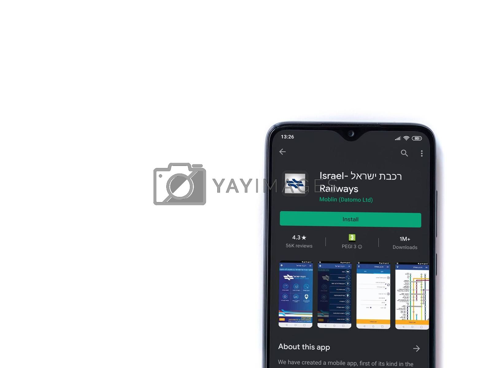 Lod, Israel - July 8, 2020: Israel Railways app play store page on the display of a black mobile smartphone isolated on white background. Top view flat lay with copy space.