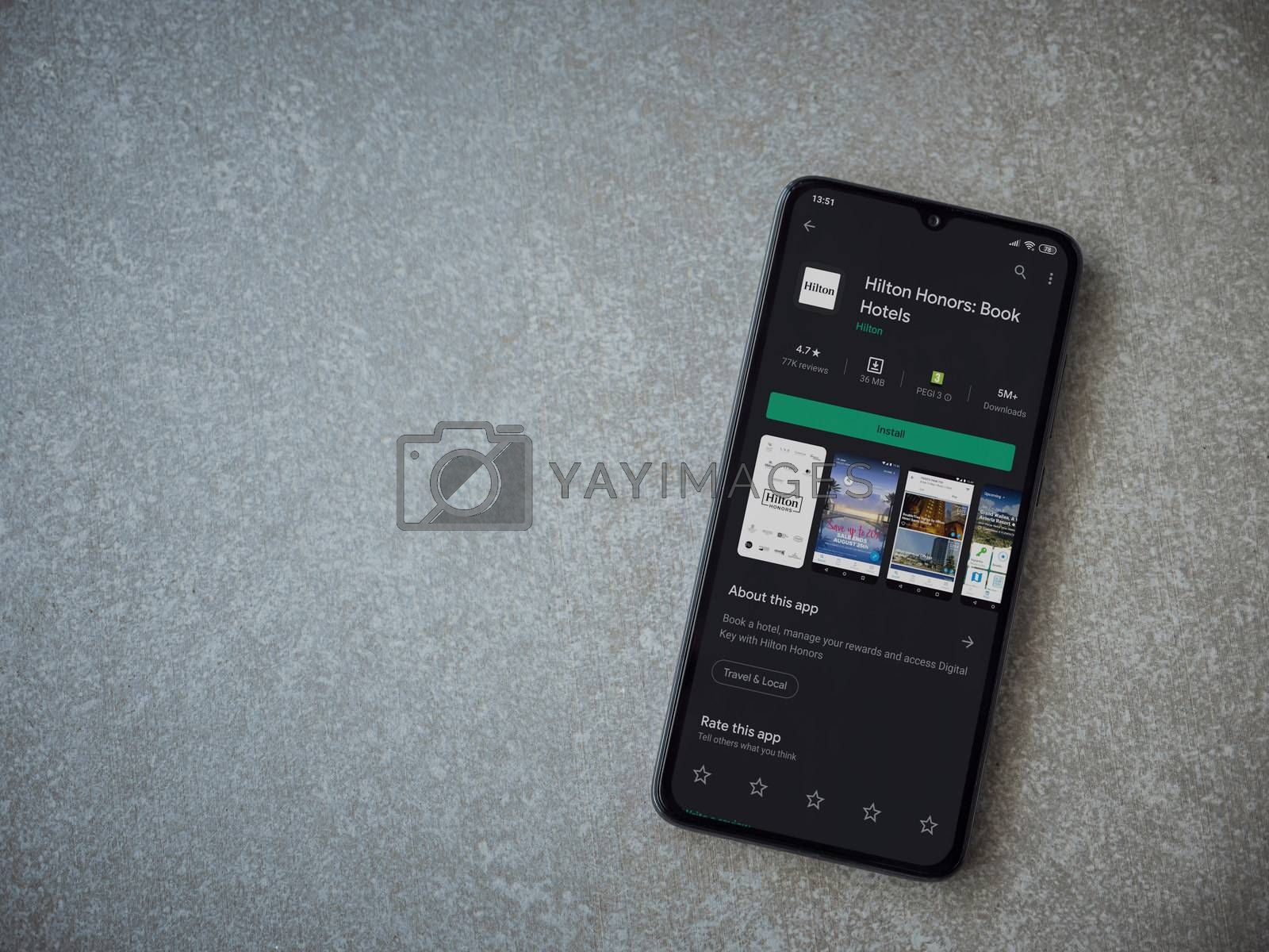 Lod, Israel - July 8, 2020: Hilton Honors app play store page on the display of a black mobile smartphone on ceramic stone background. Top view flat lay with copy space.