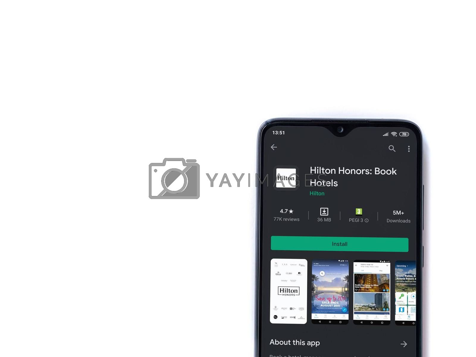 Lod, Israel - July 8, 2020: Hilton Honors app play store page on the display of a black mobile smartphone isolated on white background. Top view flat lay with copy space.