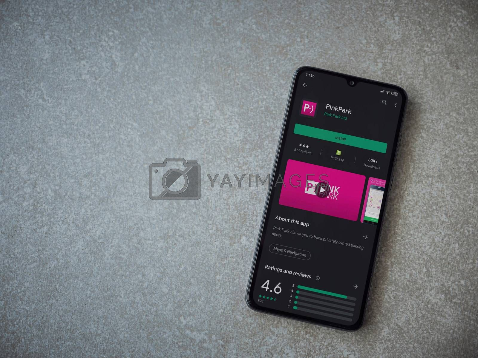 Lod, Israel - July 8, 2020: Pink Park app play store page on the display of a black mobile smartphone on ceramic stone background. Top view flat lay with copy space.