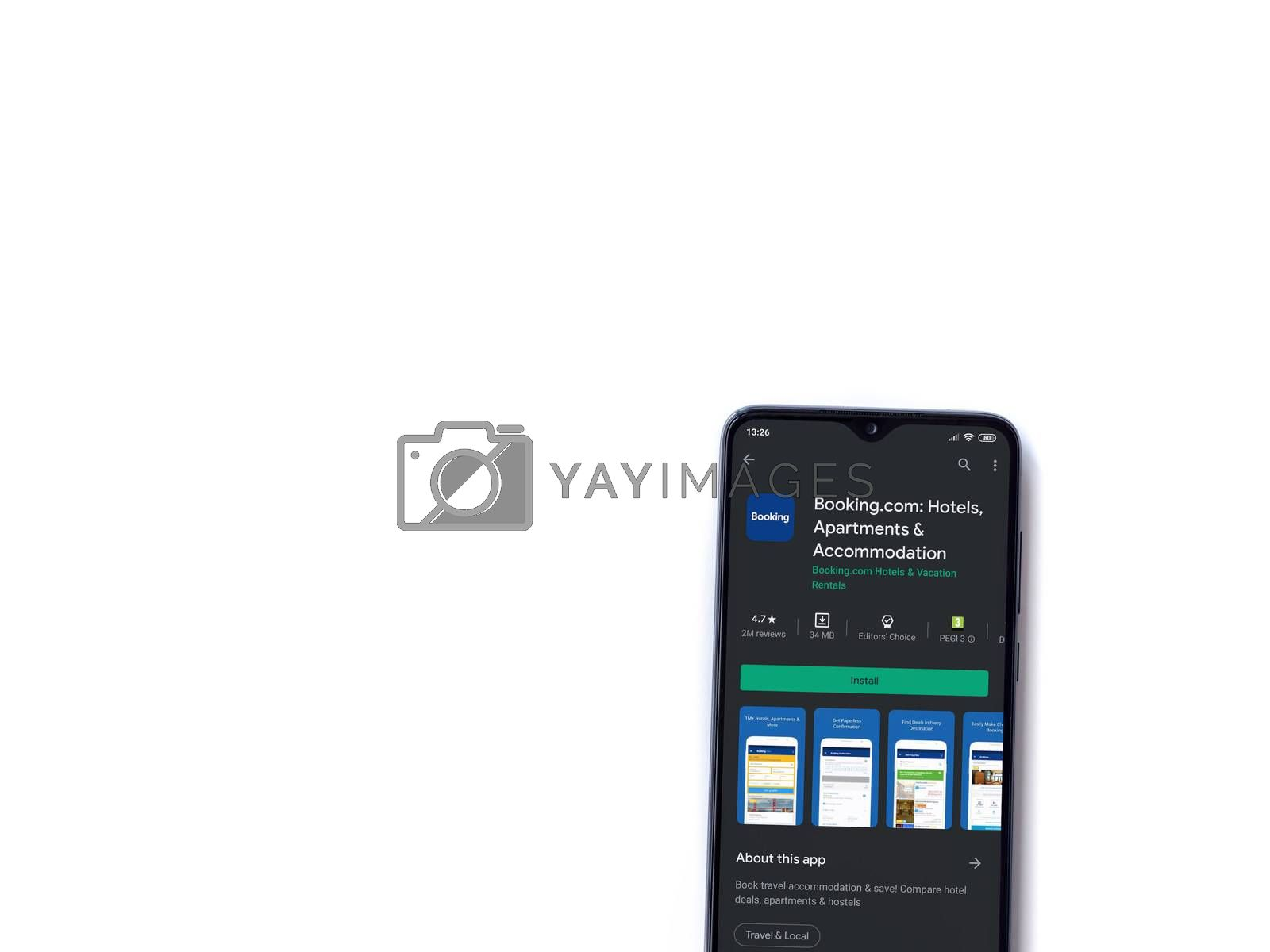 Lod, Israel - July 8, 2020: Booking.com app play store page on the display of a black mobile smartphone isolated on white background. Top view flat lay with copy space.