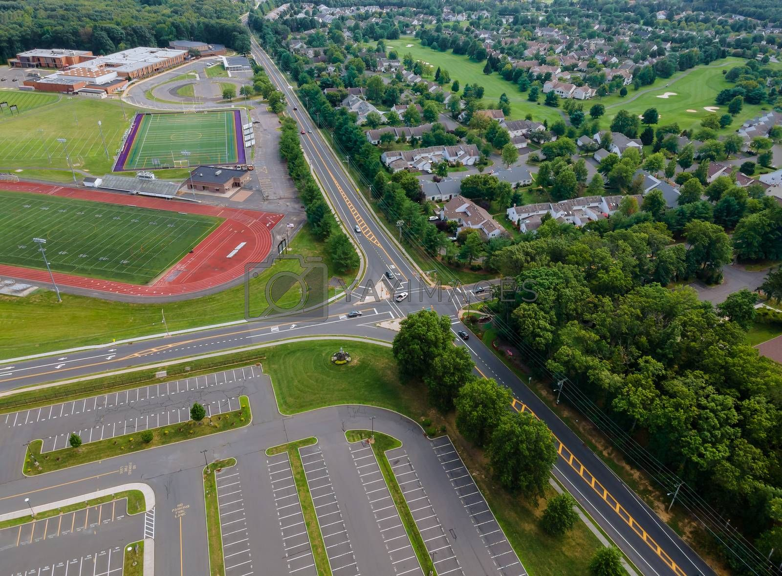 Aerial view of empty stadium with basketball field and training ground along athletic stadium running track in school in the during a pandemic
