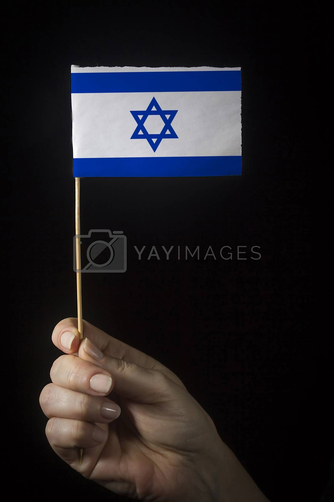 Hand with small flag of state of Israel