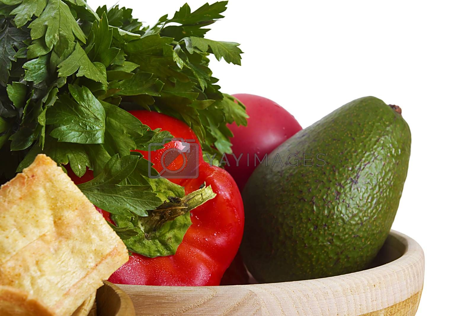 Ingredients for guacamole on white background with a dish of taco chips