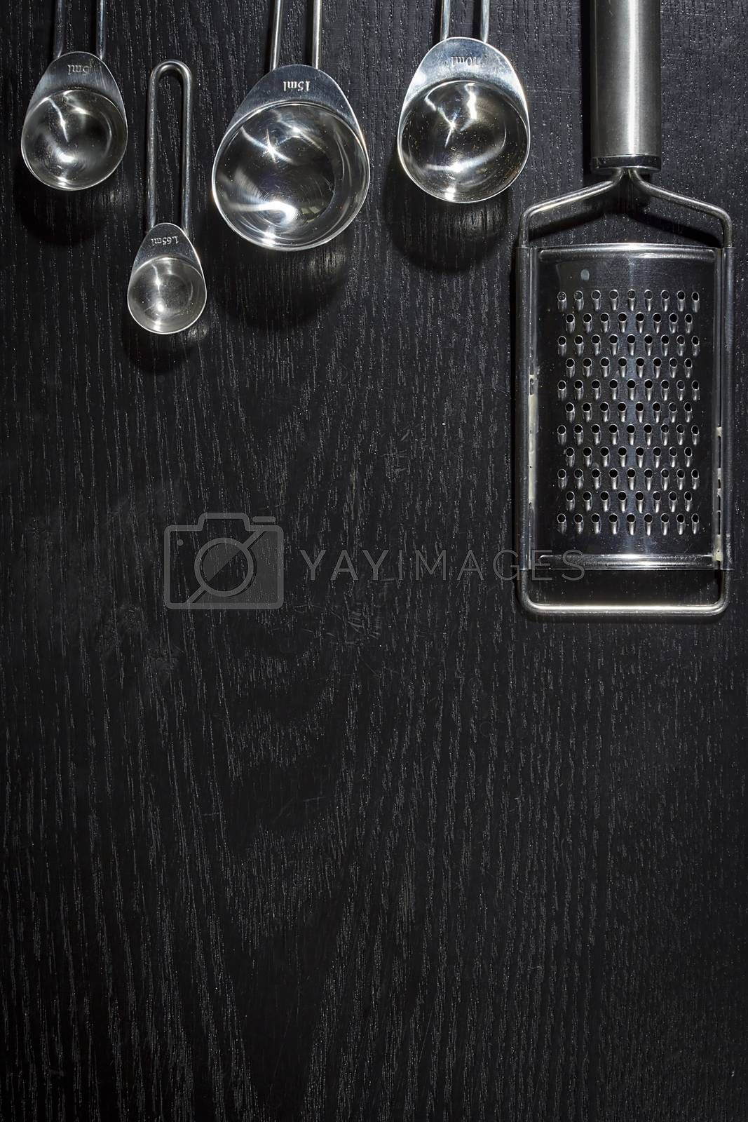 Metal measuring spoons and grater on black wooden background