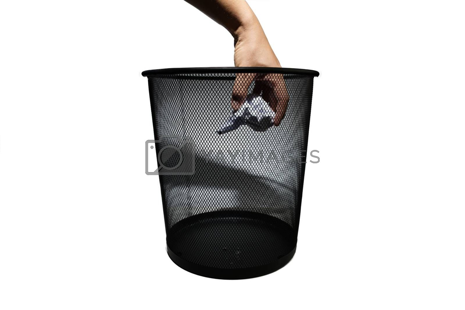 Abstract hand throwing paper scraps into black metal trash isolated white background with hand shadow.